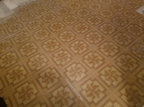 Someone put these awful peel and stick vinyl tiles over the existing vinyl flooring.